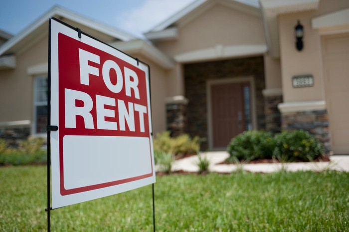 "A ""for rent"" sign placed on the front lawn in front of a single-family home."