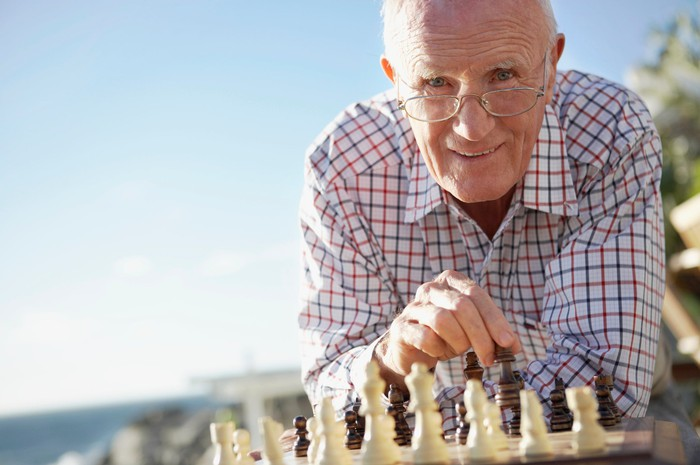 A smiling senior man playing chess at the beach.