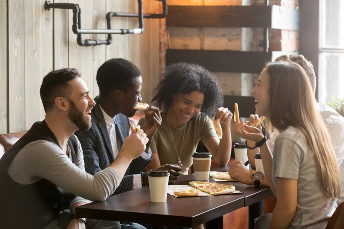 A group of young adults dine at a restaurant.