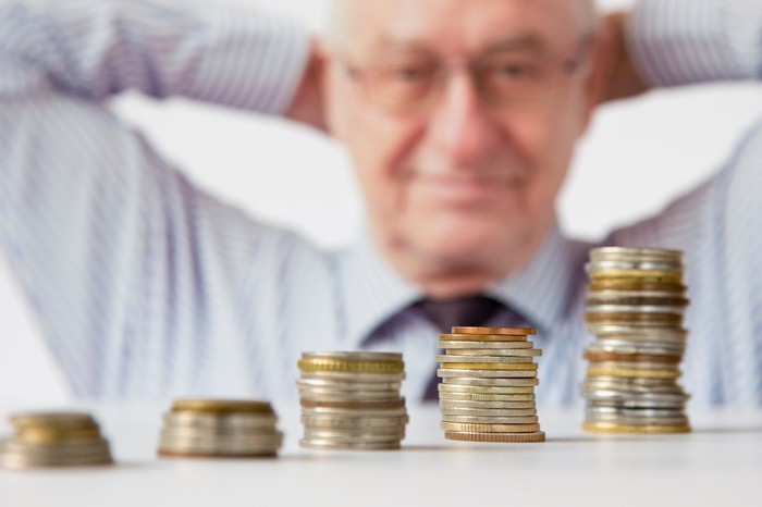 Smiling man leaning back looking at stacks of coins arranged from shortest to tallest.