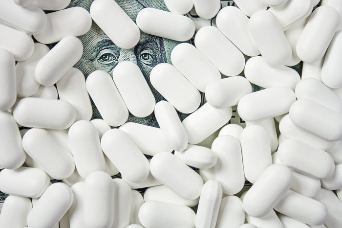Ben Franklin's eyes on a hundred-dollar bill peeking out from beneath white pills.