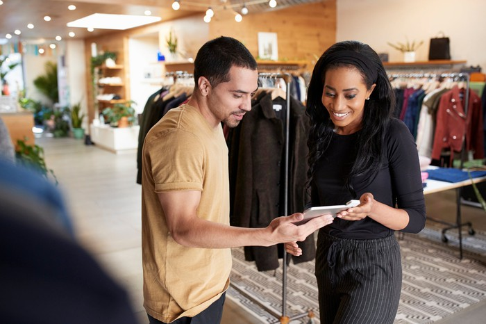 A man and a woman talk in a clothing store.