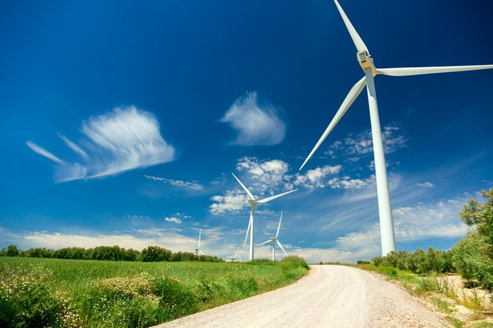 A road with wind turbines along its path.