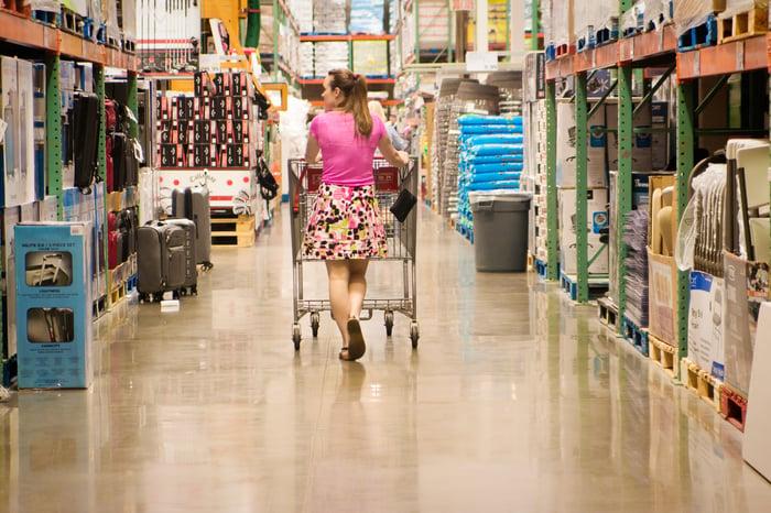 A woman pushes a shopping cart down a warehouse store aisle