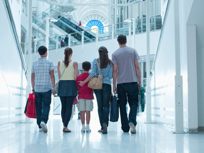 The back view of a man, woman, and three children, all carrying bags, as they walk in a shopping mall.