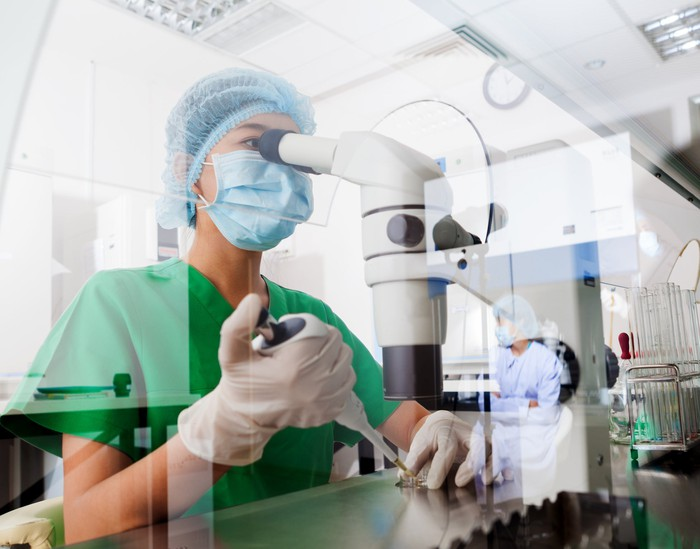 Scientist looking through a microscope in a lab