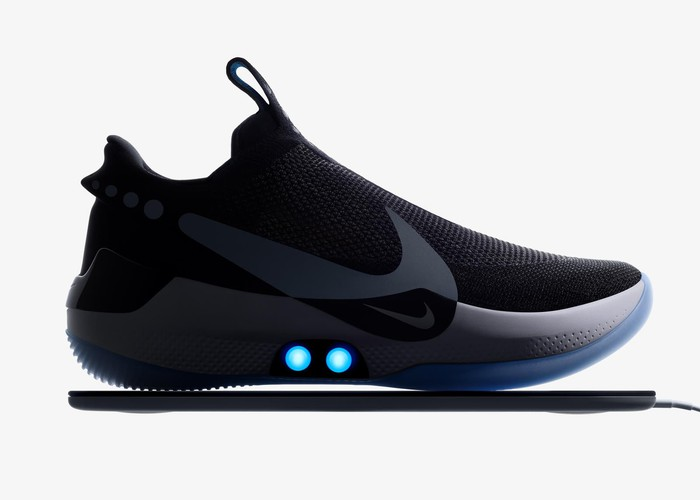 A black basketball shoe with the Nike swoosh logo on the side in gray with two blue lights on the midsole.
