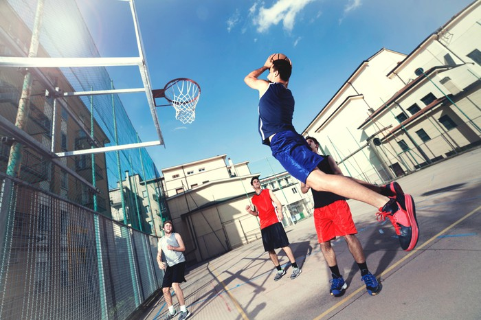 Four friends playing basketball outdoors.