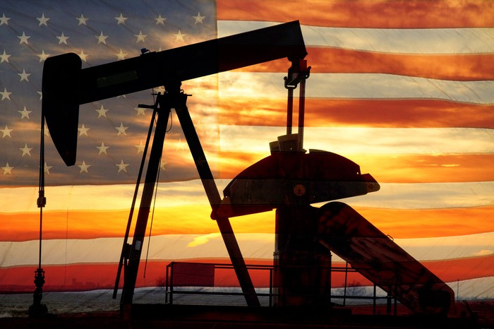An oil pump with an American flag and sunset in the background.