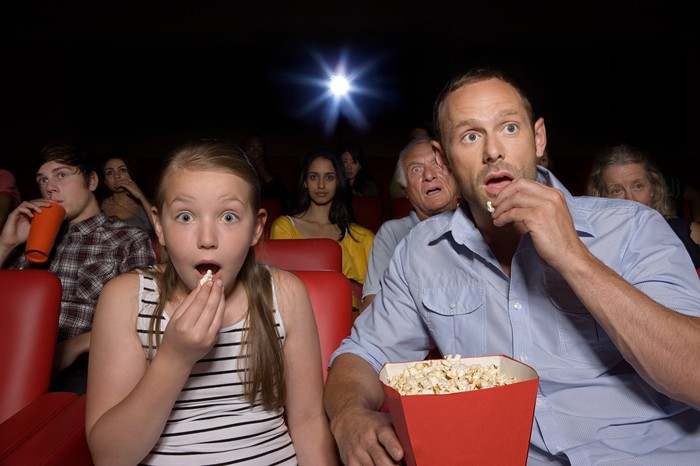 Father and daughter sharing a bucket of popcorn in a packed movie theater.