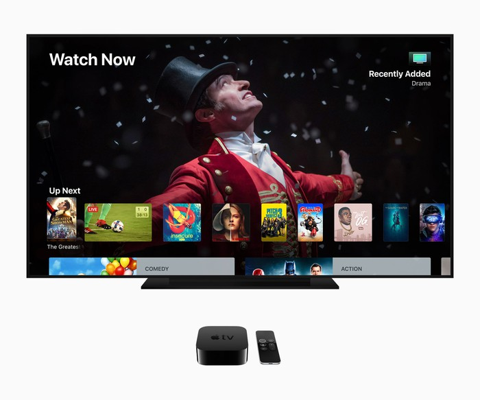 Apple TV content displayed on a TV next to an Apple TV box and Siri remote.