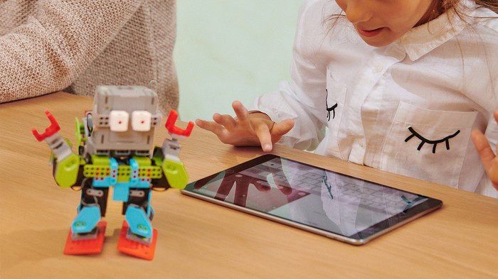 A girl using an iPad with a toy robot on the table.