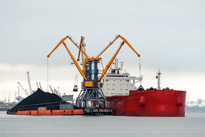 Red ship taking on cargo at a port, with large crane arms helping to load.
