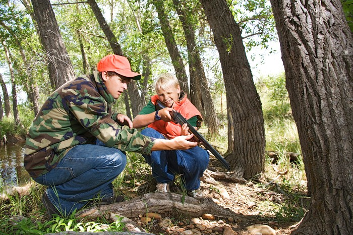 Father showing son a hunting rifle in a wooded area
