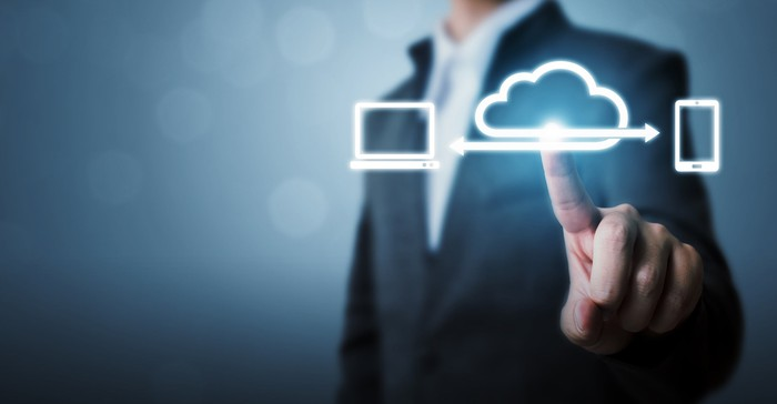 A businessman's hand pushing a cloud icon on a screen