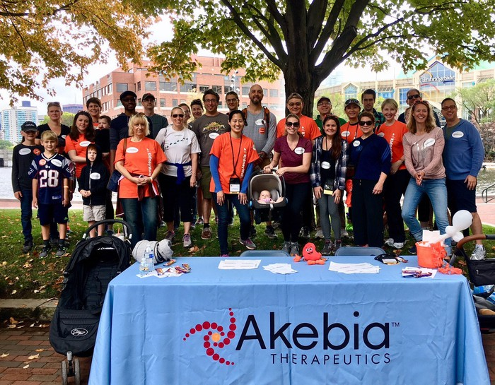 Dozens of people under a tree, behind a table with Akebia Therapeutics branding on it.