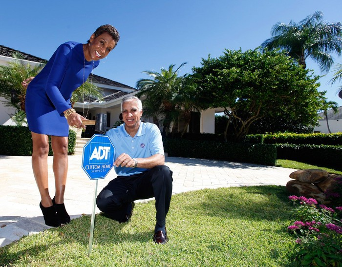 Two people standing near an ADT sign in a front yard of a home.