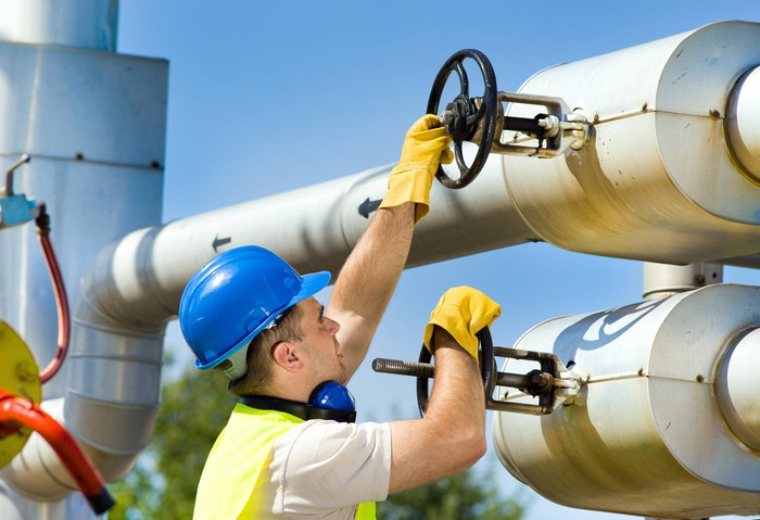 A man in a hard hat, safety vest, and gloves turning valves on an energy pipeline