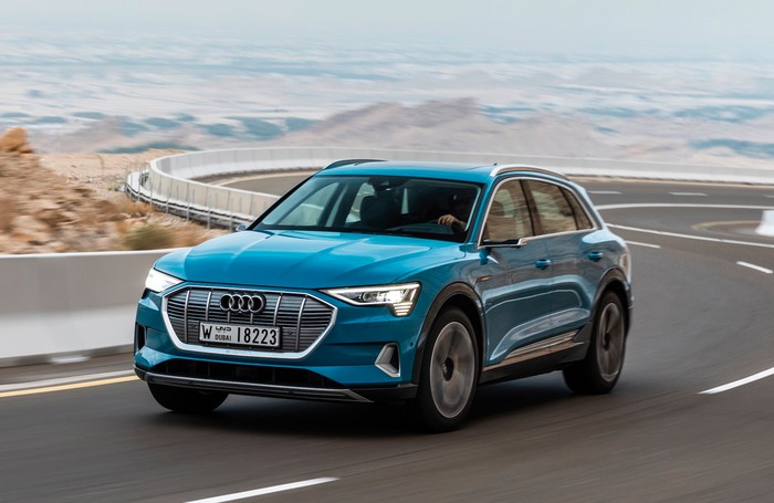 A blue Audi e-tron, a midsize electric crossover SUV, on a winding road.