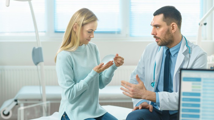 Doctor talking to woman holding a breast implant