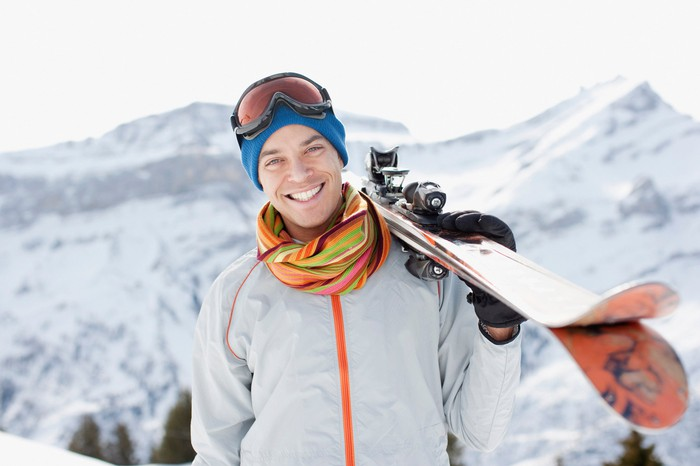 A man smiles while holding skis out in the mountains