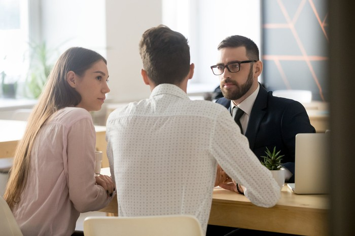 Couple sitting across the table from man in suit