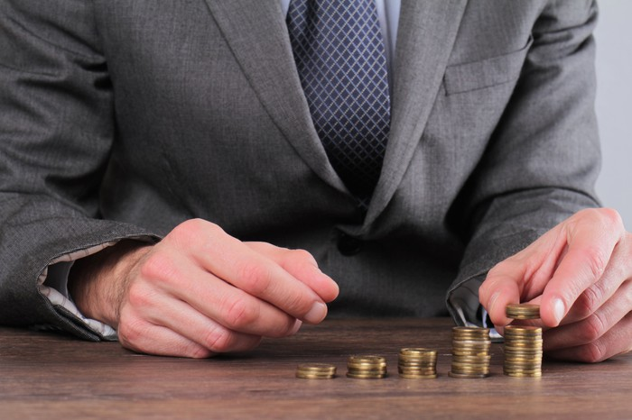 Man in suit stacking successively taller stacks of coins