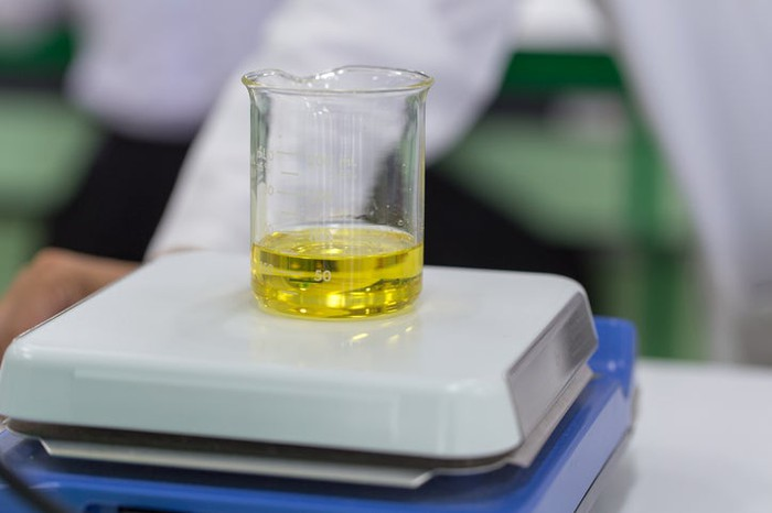 A small volume of biodiesel being weighed on a scale in the lab.