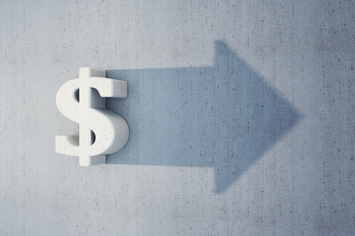 A sign of a dollar sign on a wall that's projecting a shadow in the shape of an arrow.
