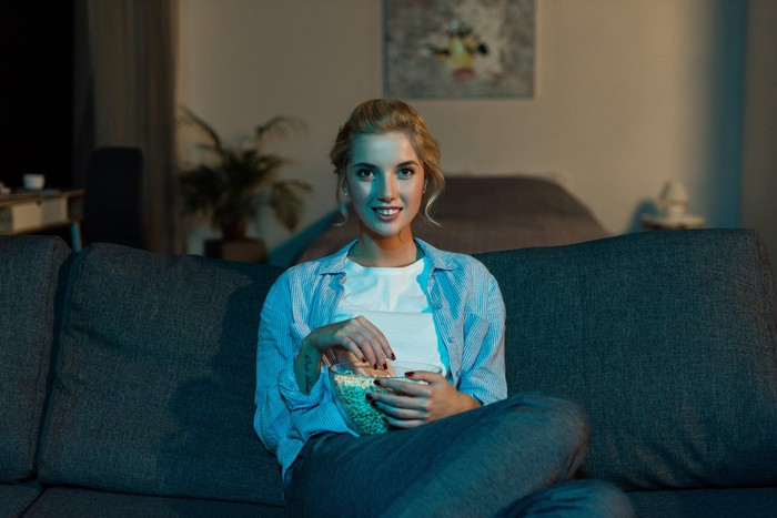 A young woman sitting on a couch watching television and eating popcorn.