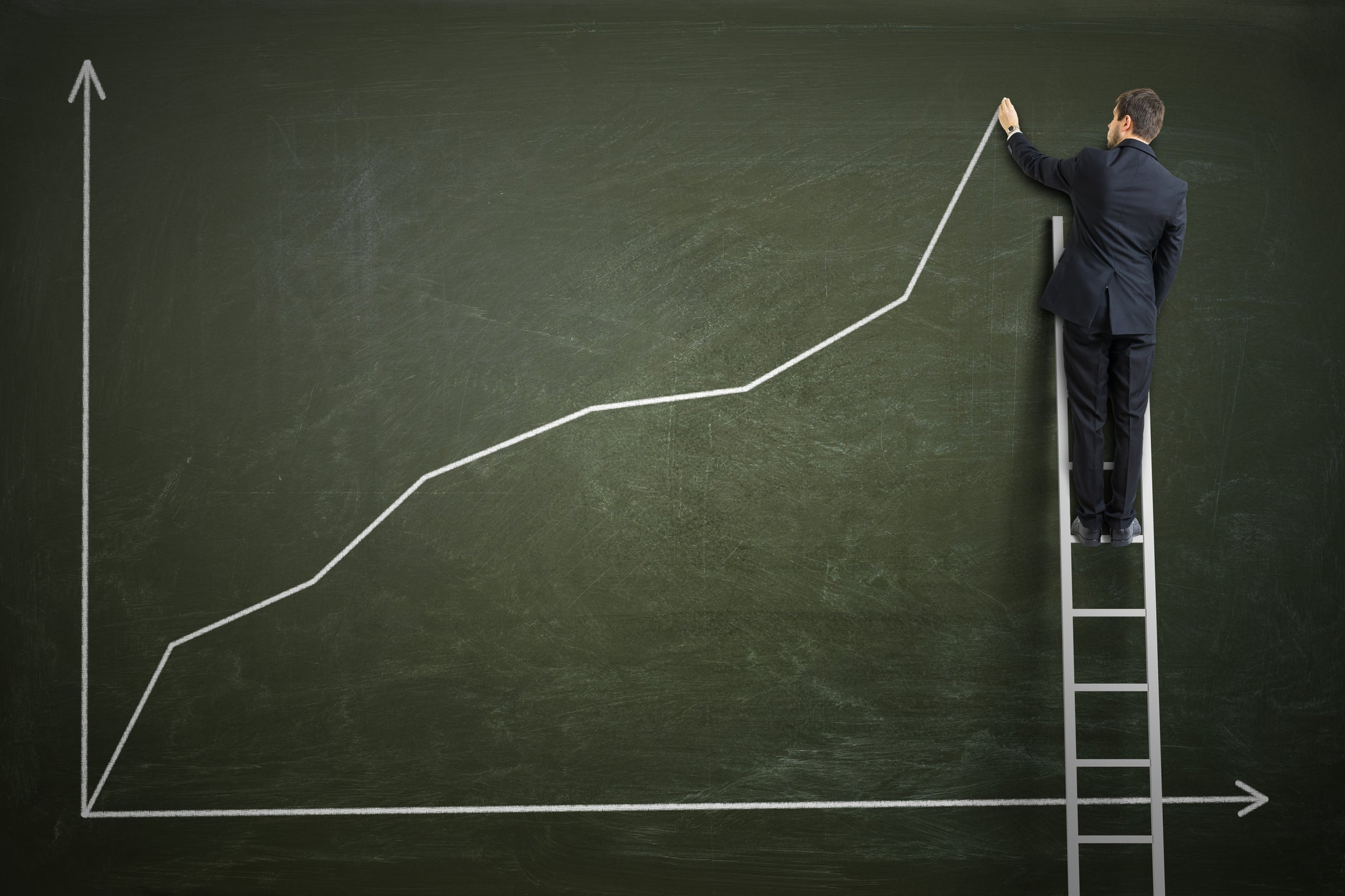 A businessman draws a rising stock chart on a blackboard.