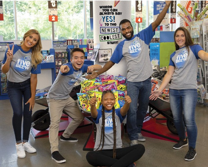 Five Five Below employees smile while posing in company T-shirts in a Five Below store.