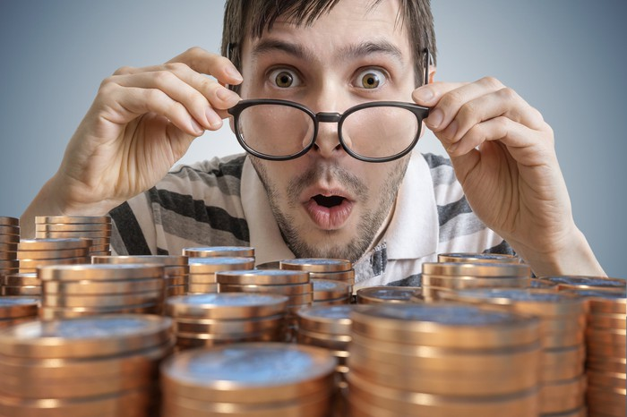 A surprised man looking at stacks of coins.
