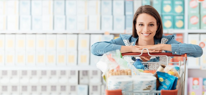 Smiling woman leaning on a grocery cart in shopping aisle