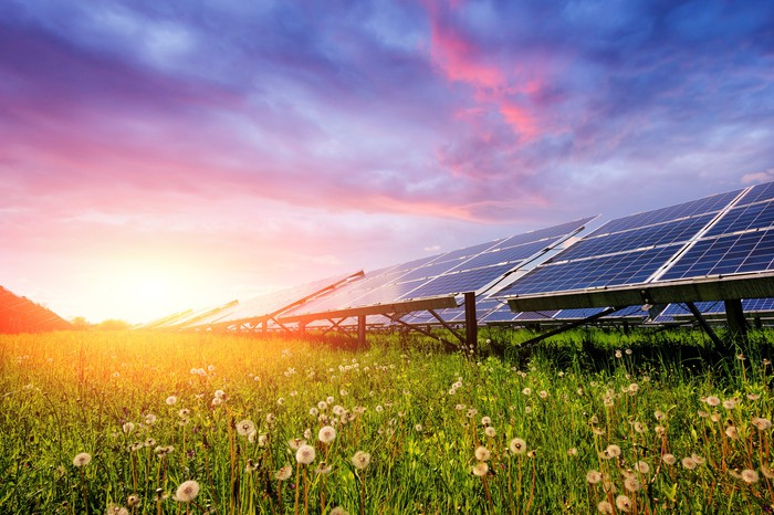 Solar panels in a field with a bright sun and a rainbow sky in the background.