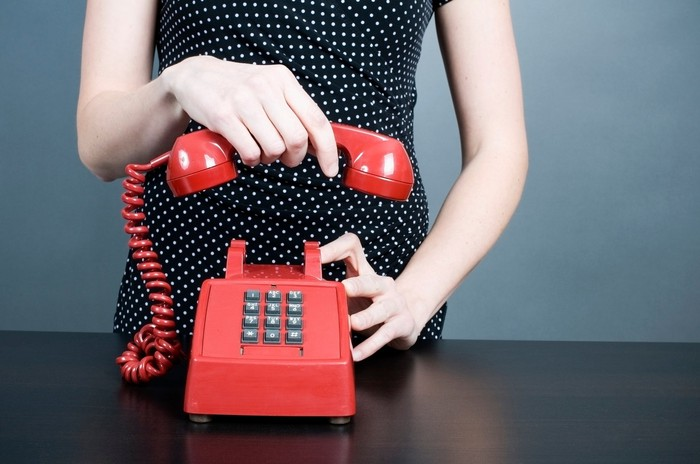 Woman hanging up a red phone