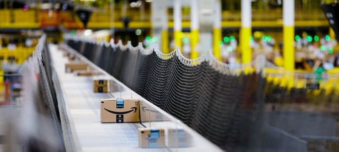 A moving belt of Amazon shipping boxes in a large warehouse facility.