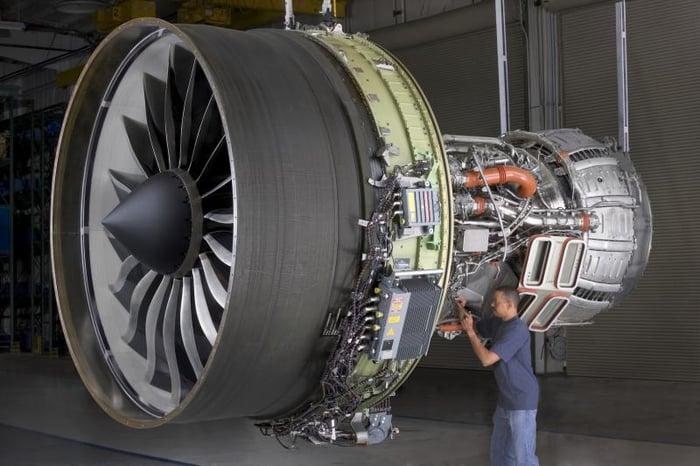 A man works on a GE aircraft turbine.