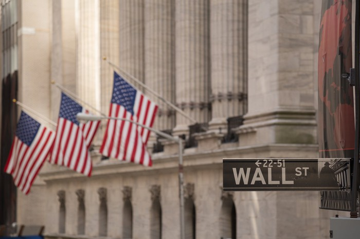A Wall St. street sign with a building and American flags in the background.
