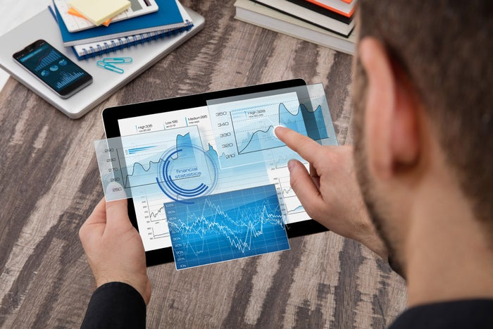 Man looking at stock charts on tablet computer