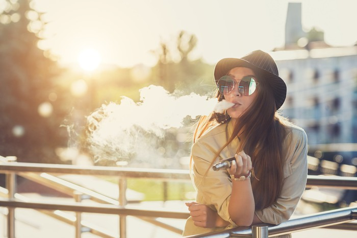 A young woman, outdoors, leaning on a railing, exhaling vapor while using an electronic cigarette.