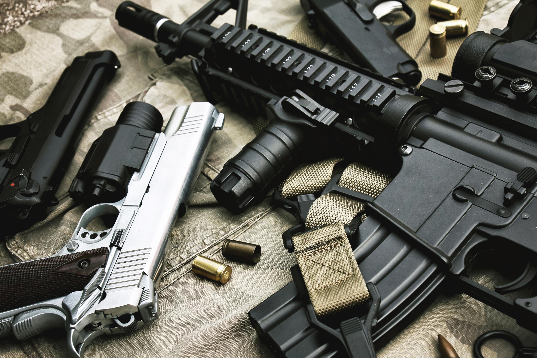 Pistols and rifle lying on camoflage fabric.