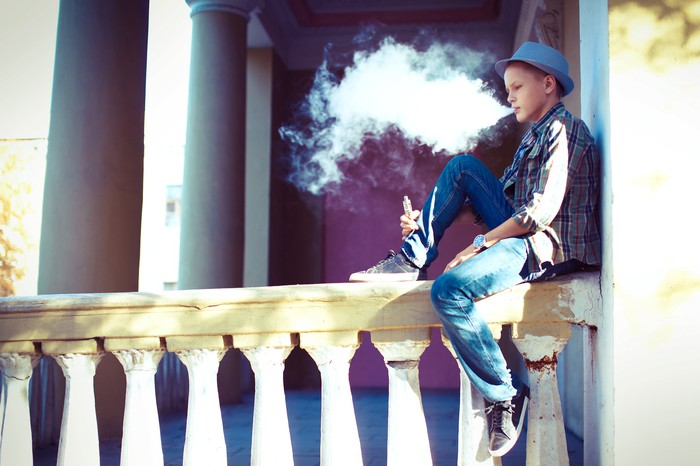 Youth sitting on a railing and vaping.