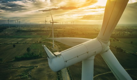 A close-up of a wind turbine with a bright sun in the background.