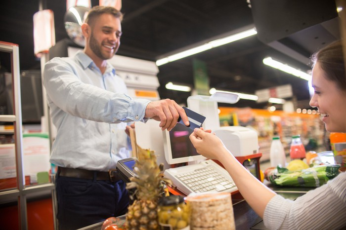 Man handing credit card to cashier in a grocery store.