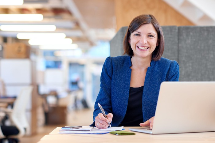 Smiling woman at desk holding a pen in her right hand and typing on a laptop with her left.