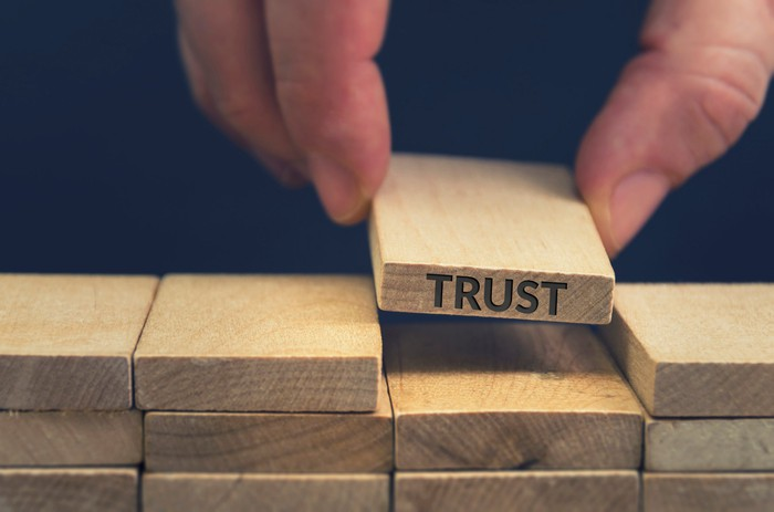 """The word """"trust"""" etched into a wooden block that's being placed into a stack of wooden blocks."""