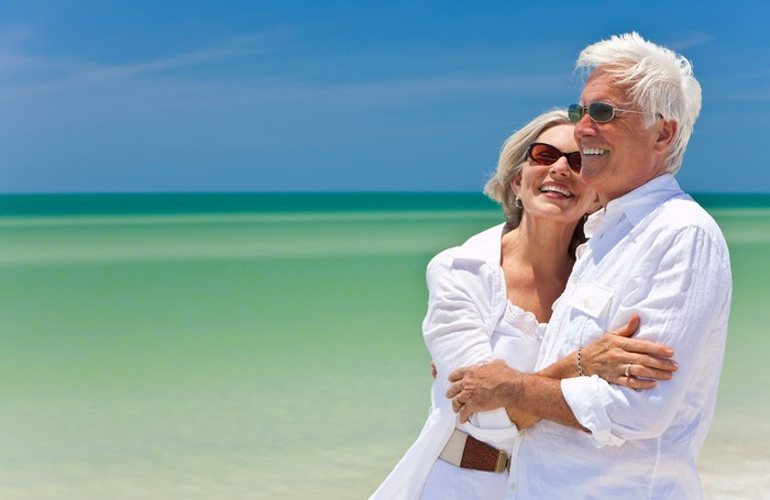 Older couple embracing at the beach
