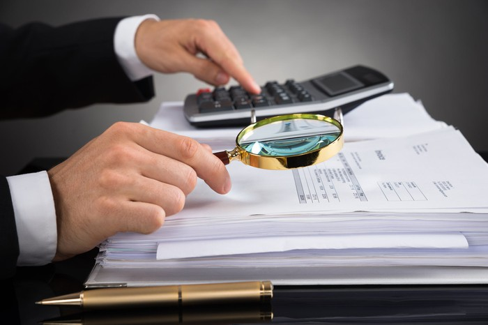 Man typing on calculator and holding magnifying glass to a pile of papers