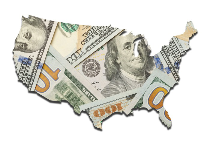 An outline of the United States that's filled in with a messy pile of hundred dollar bills.